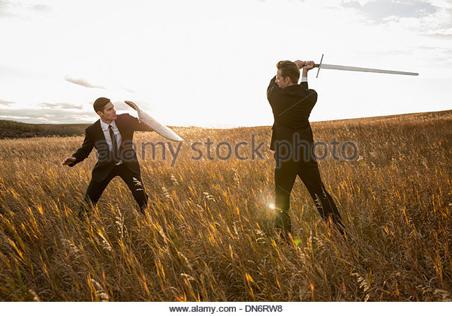 Angry businessmen fighting with sword and shield in field - Stock Image
