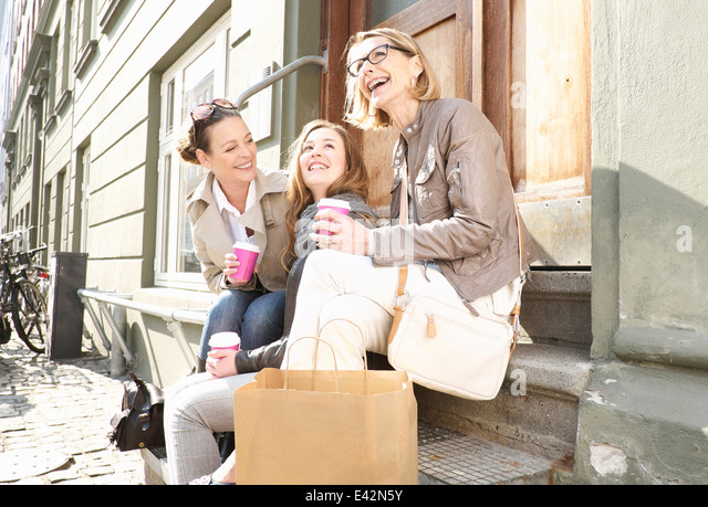 Three generation females drinking takeaway coffee on street - Stock Image