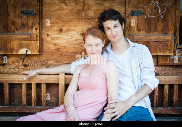 Portrait of happy couple sitting side by side - Stock Image