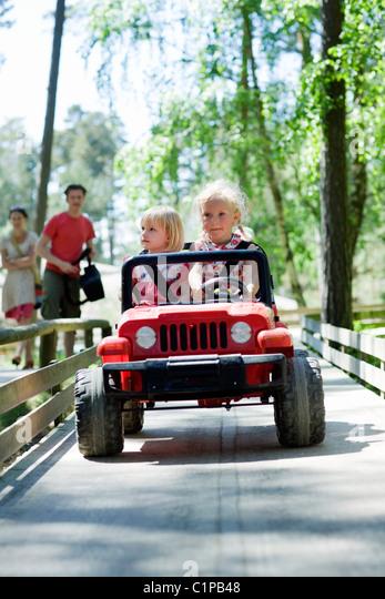 Two  girls in go-cart - Stock-Bilder