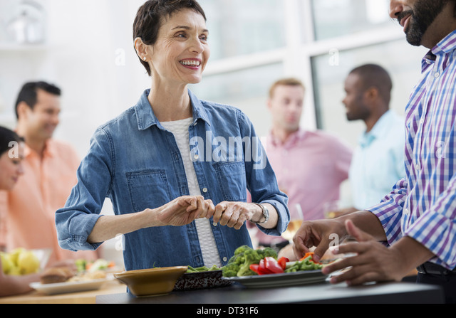 An open plan office A working lunch a salad buffet of mixed ages and ethnicities meeting together - Stock Image