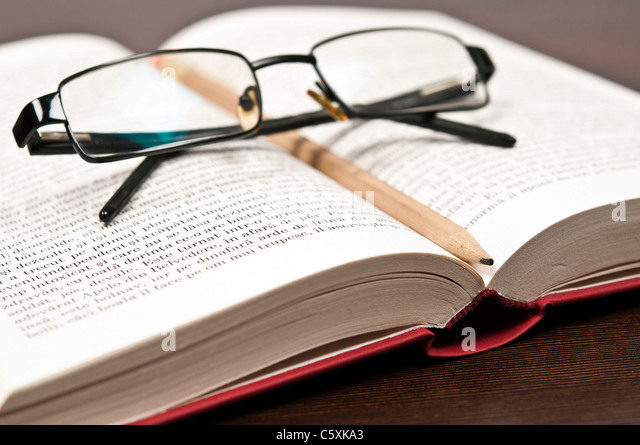 Open book and eyeglasses on desk - Stock Image