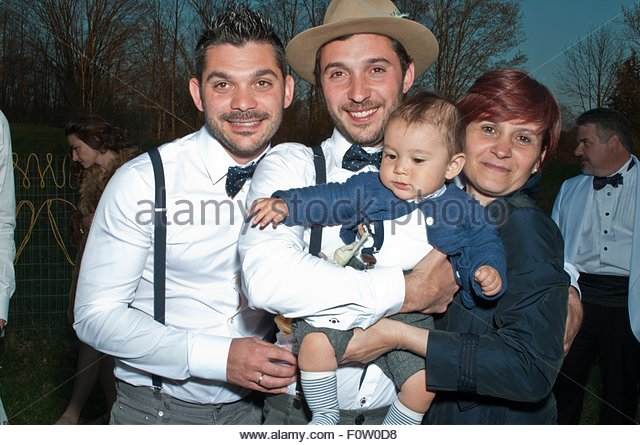 Portrait of groom holding baby boy, standing with family and friends, at wedding - Stock-Bilder