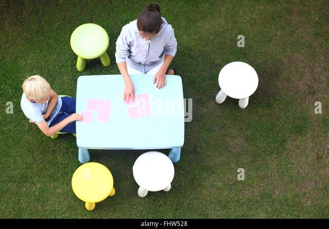 Fun outdoor activities. Creative fun way to boredom. Children play in the garden, they draw with crayons - Stock-Bilder