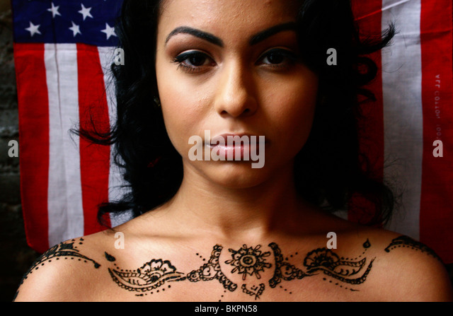 Close up portrait of woman with henna body art on her shoulders, and the American flag as the background. - Stock-Bilder