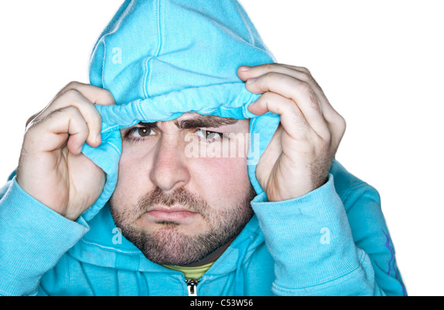 A caucasian male with a quizzical expression pulls his hood down over his forehead. - Stock Image