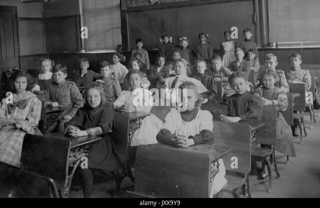 Full length landscape shot of schoolchildren seated at desks, African American students standing in the back, 1920. - Stock Image