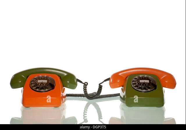 An orange and a green telephone with receivers in reversed colours - Stock Image
