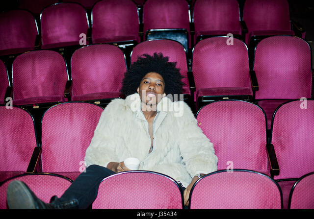Portrait of a young man in a fur coat in a theater - Stock Image