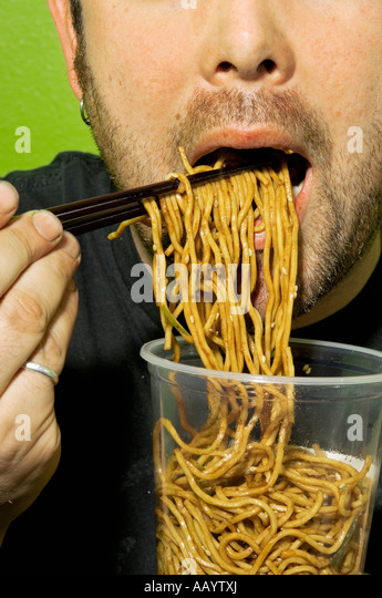 Man eating noodles with chopsticks. - Stock Image