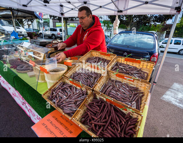 Market trader and sausage stall, France. - Stock Image