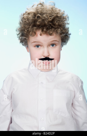 Portrait of a boy wearing a fake moustache - Stock Image
