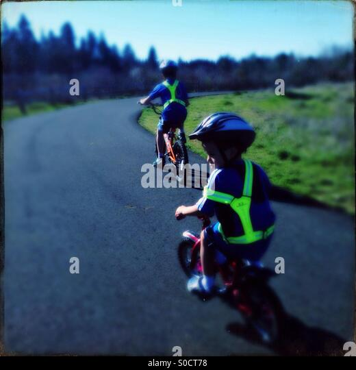 Two boys riding bicycles on path in a park on a sunny day wearing safety vests and helmets - Stock Image