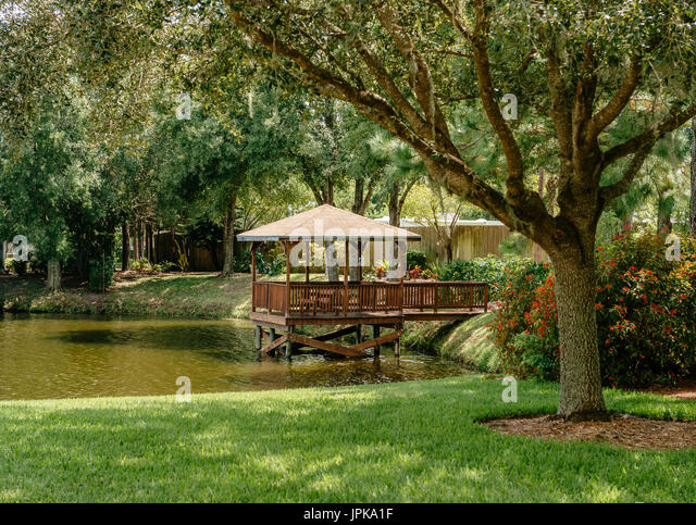 A quiet, secluded wooden gazebo on a small lake in a residential subdivision in Florida, USA. - Stock Image
