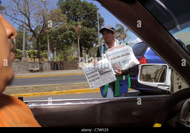 Nicaragua Managua street scene car traffic driver newspaper vendor headline government corruption Hispanic man - Stock Image