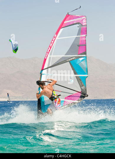 A windsurfer performing tricks on the red sea at the resort of Eilat in Israel. - Stock Image