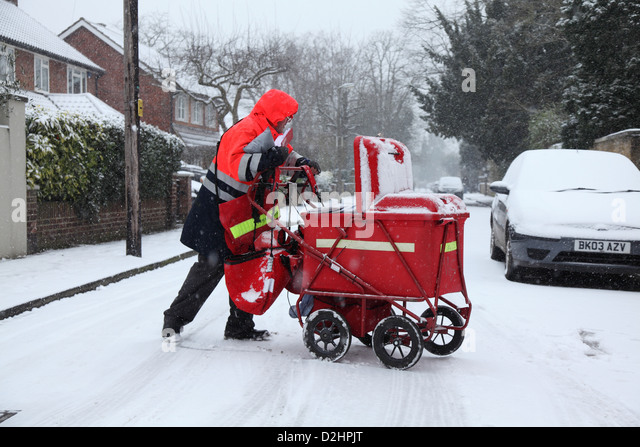 Postman delivers the mail in  a snowfall. - Stock Image