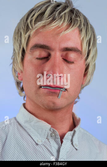 Zipper on mouth silences silly blonde haired man - Stock Image