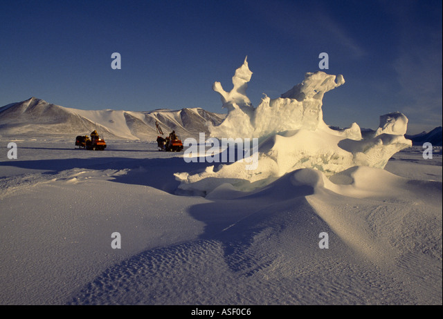 Broken sea ice sculpted by wind and sun Fast sea ice near coastline Two Skidoos personnel McMurdo Sound Antarctica - Stock Image