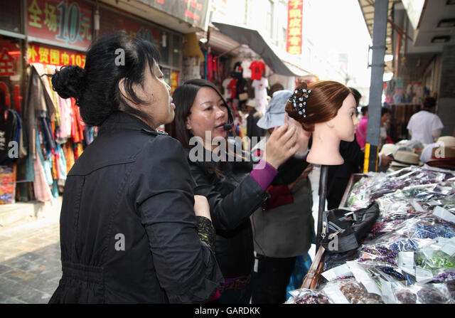 A woman combs and puts together a wig on a mannequin at a galanterie, she  talks on a microphone and shows a potential - Stock Image