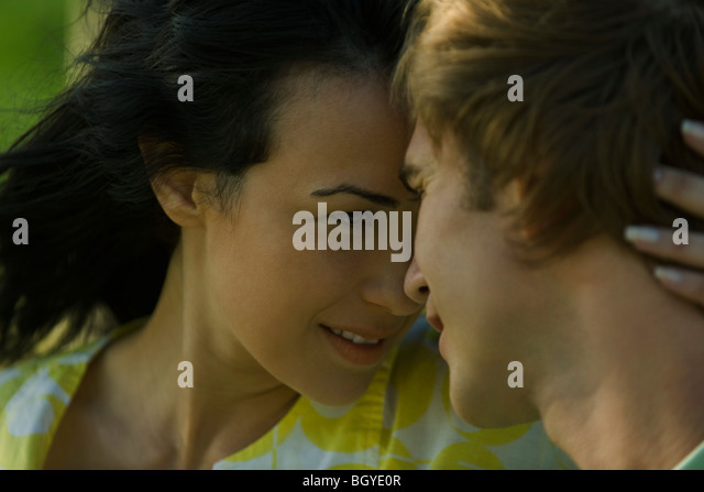 Young couple looking into each other's eyes, foreheads pressed together - Stock-Bilder