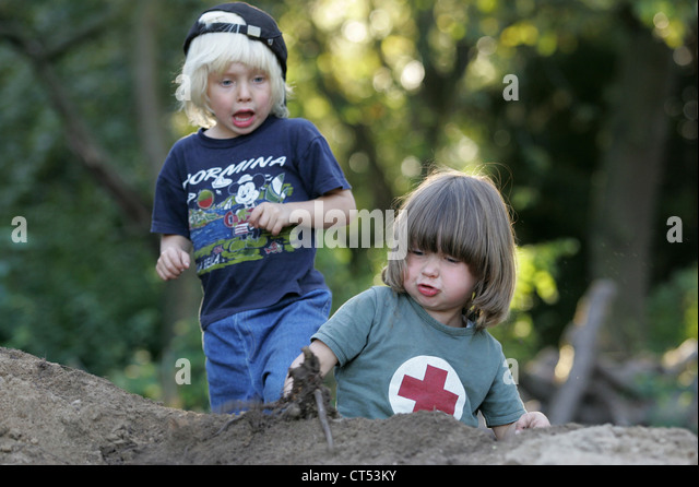 Two boys playing on a sand pile - Stock Image