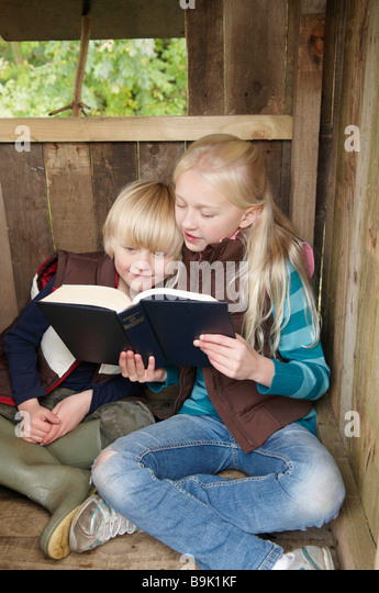 Girl reading story to young boy - Stock Image