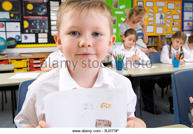 School boy displaying artwork in classroom - Stock Image