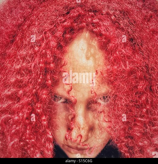 Girl peering out from behind red crimped Halloween wig - Stock-Bilder