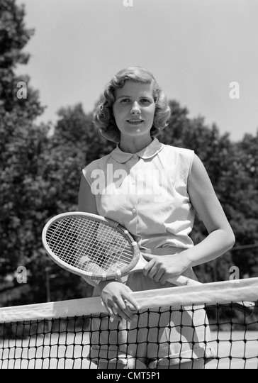 1950s PORTRAIT WOMAN HOLDING TENNIS RACQUET STANDING BEHIND NET OUTDOOR LOOKING AT CAMERA - Stock Image