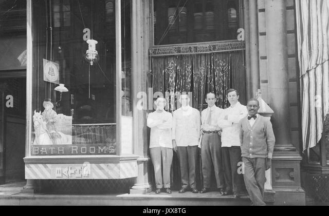 Four mature Caucasian men and one mature African American man, possibly dressed as waitstaff, stand in front of - Stock Image