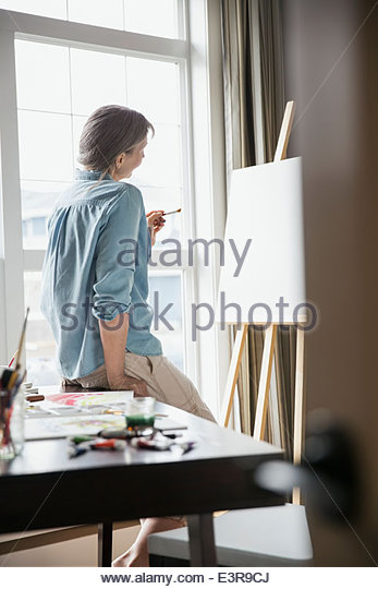 Woman painting at easel - Stock Image