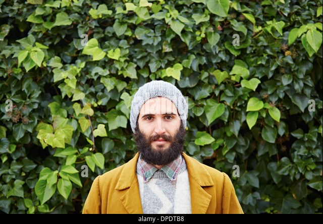 Smiling hipster bearded male student in vintage clothes - Stock Image