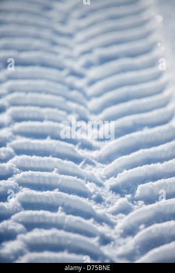 Car winter tire tracks on snow - Stock Image