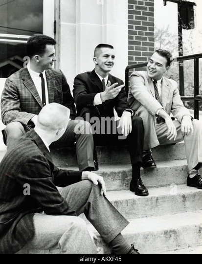 Four young men sitting on outdoor stairs 1950 s - Stock Image