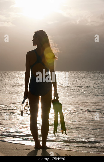 Silhouette of woman at water's edge, Mustique, Grenadine Islands - Stock Image