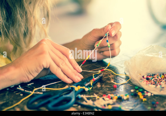 woman hands making craft crafting hobby bracelet colorful 'pass through' threading beading beads rope - Stock Image