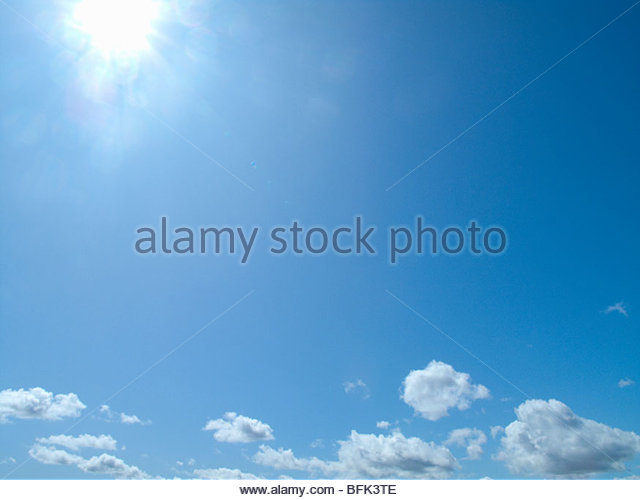 Sun shining in blue sky with clouds - Stock Image