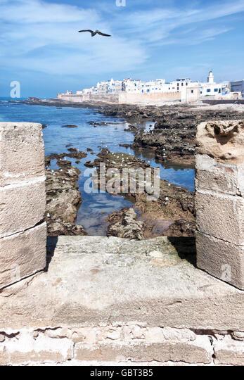 Coastal town Essaouira with sea and seagulls against cloudy blue sky. - Stock Image
