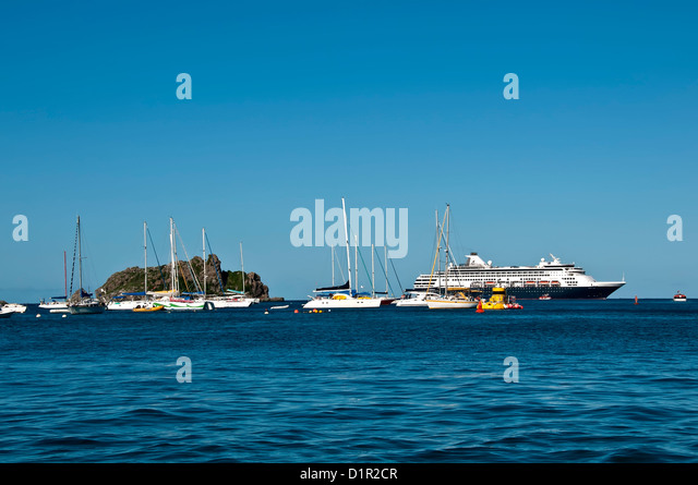 Gustavia harbor entrance with anchored sailboats and large cruise ship, Saint Barthelemy - Stock Image
