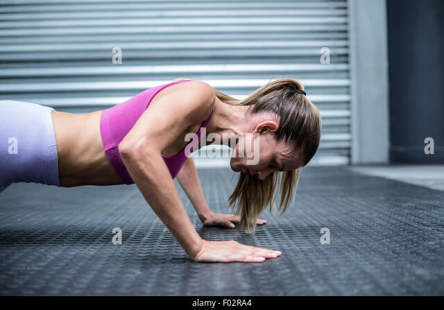 Muscular woman doing push ups - Stock Image