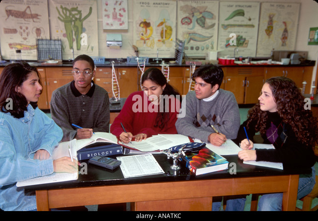 New Jersey Englewood high school science lab students discuss project Black male Hispanic Asian fremale teens writing - Stock Image