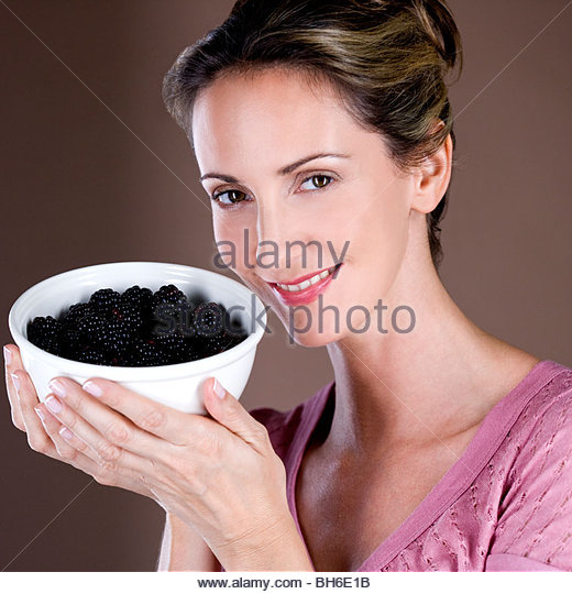 A mid adult woman holding a bowl of blackberries - Stock-Bilder