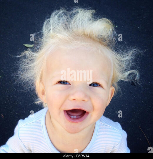 Portrait of a laughing boy with windswept hair - Stock Image