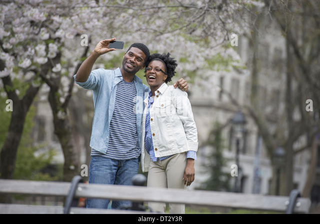 A couple side by side taking a photograph with a smart phone - Stock Image