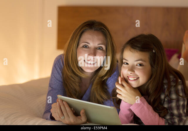 Mother and daughter using digital tablet on bed - Stock Image