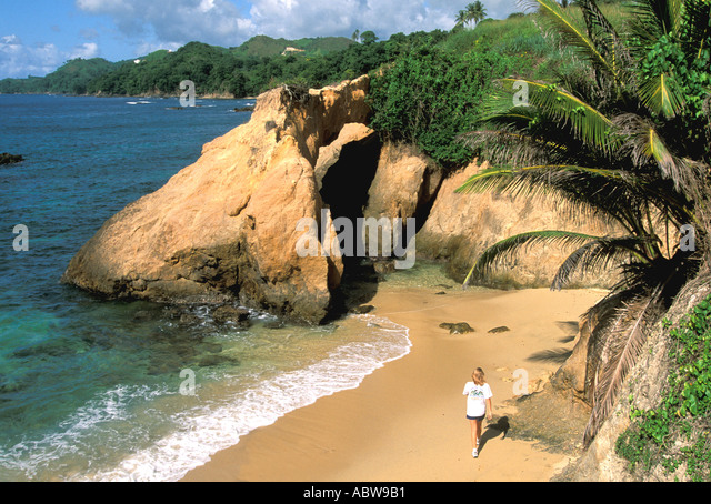 Caribbean Tobago Woman walking on beach with cliffs and rocks - Stock Image