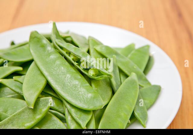 Sugar snap peas on plate - Stock Image
