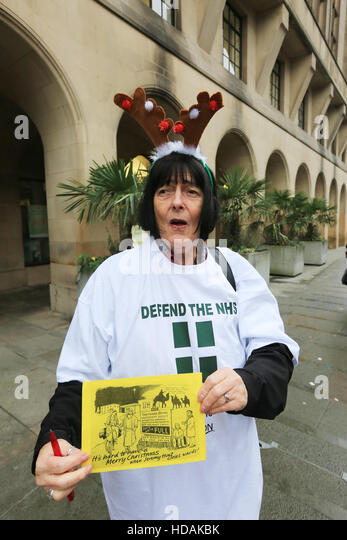 Manchester, UK. 10th Dec, 2016. A 'Defend The NHS' campaigner holding a Xmas protest card to Jeremy Hunt, - Stock Image