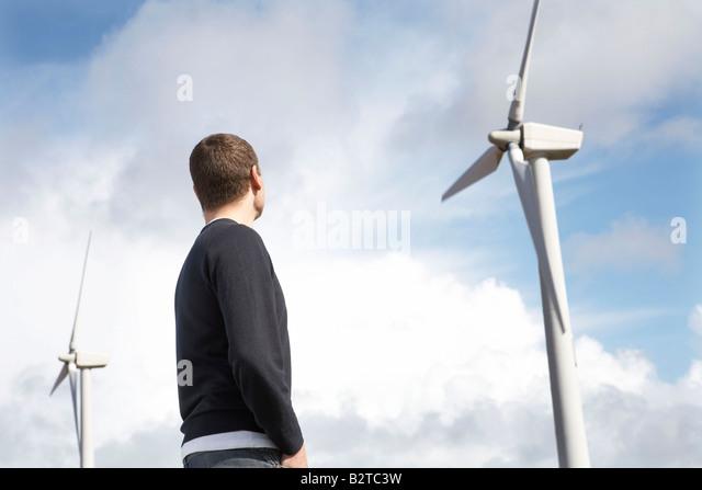 Man looking at wind turbines - Stock Image